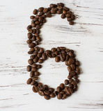 Numeral  from the grains of coffee on a light wooden background. Selective focus. The number six nine lined with grains of coffee on light background old board Royalty Free Stock Photos