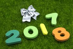 Numeral 2017 2018 on green grass with silver Christmas bow stock images
