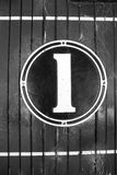 Numeral one, old fashioned sign, on circular cast metal and painted, mounted on wooden panelled wall Stock Images