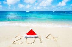 Numere 2014 con el sombrero de la Navidad en la playa arenosa Foto de archivo