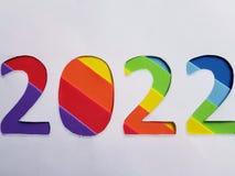 numere 2022 con espumoso en el fondo del color del arco iris y blanco Fotografía de archivo libre de regalías