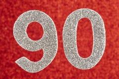 Numere a cor de prata noventa sobre um fundo vermelho anniversary Imagem de Stock