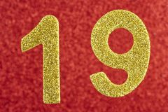 Numere dezenove cores amarelas sobre um fundo vermelho anniversary Fotografia de Stock