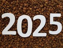 numere 2025 en blanco con el fondo asado de los granos de café Imágenes de archivo libres de regalías