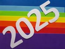 numere 2025 en blanco con espumoso en fondo de los colores del arco iris Imagenes de archivo