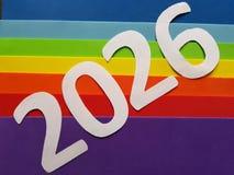 numere 2026 en blanco con espumoso en fondo de los colores del arco iris Foto de archivo libre de regalías