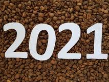 numere 2021 en blanco con los granos de café asados fondo, diseño por Año Nuevo Fotografía de archivo