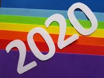 numere 2020 en blanco y espumoso en fondo de los colores del arco iris Foto de archivo