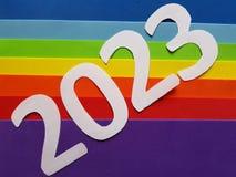 numere 2023 en blanco y espumoso en fondo de los colores del arco iris Imagenes de archivo