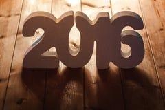 Numere 2016 en el fondo de madera de la tabla, plantilla del Año Nuevo Imagen de archivo libre de regalías