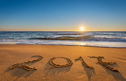 Numere 2017 escrito en la arena de la costa en la salida del sol Imagen de archivo libre de regalías