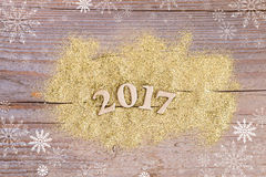 Numere 2017 no fundo de madeira com brilho dourado Foto de Stock Royalty Free