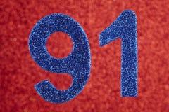 Numere a noventa-um cor azul sobre um fundo vermelho anniversary Imagem de Stock