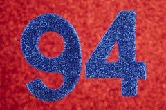 Numere noventa y cuatro colores del azul sobre un fondo rojo aniversario Imagenes de archivo
