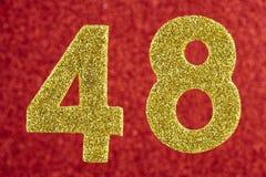 Numere quarenta e oito cores do ouro sobre um fundo vermelho anniversary Imagem de Stock Royalty Free