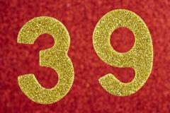 Numere trinta e nove cores do ouro sobre um fundo vermelho anniversary Fotografia de Stock Royalty Free