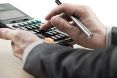 Numeri calcolatori del bilancio dell'uomo di finanza di affari fotografia stock libera da diritti