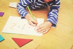 Numeri di scrittura del ragazzino, istruzione iniziale Fotografia Stock
