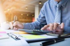 Numeri, fatture e fi calcolatori del bilancio dell'uomo di finanza di affari Immagine Stock