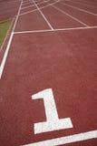 Numeri un cartello in una pista corrente atletica Immagine Stock Libera da Diritti