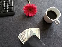 Numeric keyboard of a computer, gerbera flower, coffee cup and black wallet with american dollars banknotes on the gray desk. Objects in workspace for business stock photos