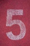 Numero cinque sulla pista corrente Numero bianco della pista sulla pista di gomma rossa Immagini Stock