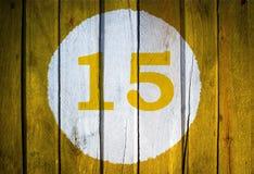 Numero civico o data di calendario nel cerchio bianco su giallo tonificato Fotografia Stock Libera da Diritti
