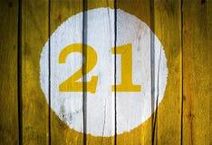 Numero civico o data di calendario nel cerchio bianco su giallo tonificato Immagini Stock