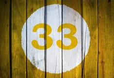 Numero civico o data di calendario nel cerchio bianco sul wo tonificato giallo Fotografia Stock Libera da Diritti