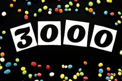 Numero 3000 con la caramella multicolore intorno su fondo nero Fotografia Stock