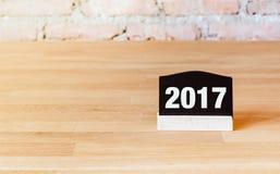Numero del nuovo anno 2017 sul segno della lavagna sulla tavola di legno al mattone w Fotografia Stock Libera da Diritti