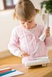 Numero della manopola della bambina sul telefono in salotto Fotografia Stock