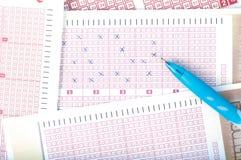 Numero di marcatura della mano del ` s della persona sul biglietto di lotteria con la penna vincita fotografie stock libere da diritti