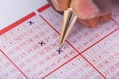 Numero di marcatura della persona sul biglietto di lotteria immagini stock libere da diritti