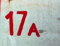 Numero diciassette A disegnato da pittura rossa sulla parete Whitewashed Facciata misera del gesso dello scaffale del ¡ di With D fotografia stock libera da diritti