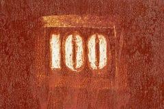 Numero 100 dipinto su una vecchia superficie arrugginita Fotografie Stock Libere da Diritti