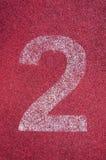 Numero due sulla pista corrente Numero bianco della pista sulla pista di gomma rossa Fotografia Stock