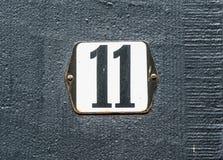 Numero nero del numero civico 11 sul piatto bianco fotografia stock
