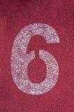 Numero sei sulla pista corrente Numero bianco della pista sulla pista di gomma rossa Immagine Stock Libera da Diritti