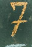 Numero sette scritto il gesso della mano a bordo Testo numero sette sulla lavagna Immagine Stock