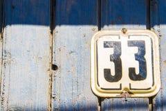 Numero 33 sulla parete blu di legno della crepa Fotografia Stock Libera da Diritti