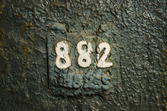 Numerology or magic of digits 882. Number 882 eight hundred eighty two, painted with white paint on the wall covered with grunge peeled off green and blue broken Stock Photos