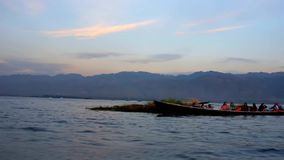 Evening on Inle Lake, Myanmar. Numerous canoes with tourists wait for the sunset on Inle Lake and enjoy the show of traditional leg-rowing fishermen, Myanmar stock footage
