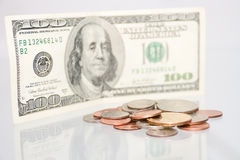 Numerous coins against one hundred dollar bill Stock Images