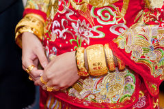 Numerous golden wedding bangles on Chinese bride Royalty Free Stock Photo