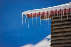 Numerous icicles on the edge of a cabin roof at Balea Lake, Romania. Numerous icicles on the edge of a wooden cabin roof at Balea Lake, Romania Stock Photo