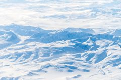 Numerous mountains and valleys covered by snow. Numerous mountains and valleys covered by white snow royalty free stock photography