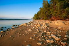 Numerous rocks lying along lake shore near thick forest stock photography