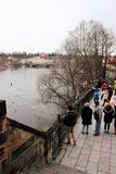 Prague, Czech Republic, January 2015. Numerous tourists on the embankment of the Vltava river look at the birds on the water. royalty free stock photos