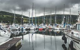 Numerous yachts at the Northern Ireland pier. Rainy cloudy sky background. Small touristic ships at the bay. Reflection in the water surface. Luxury lifestyle stock photography